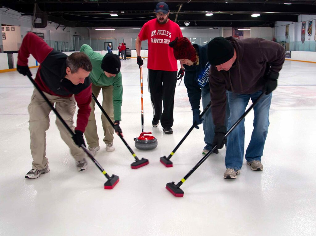 Four learn-to-curl participants sweeping in front of a stone with an instructor behind them.