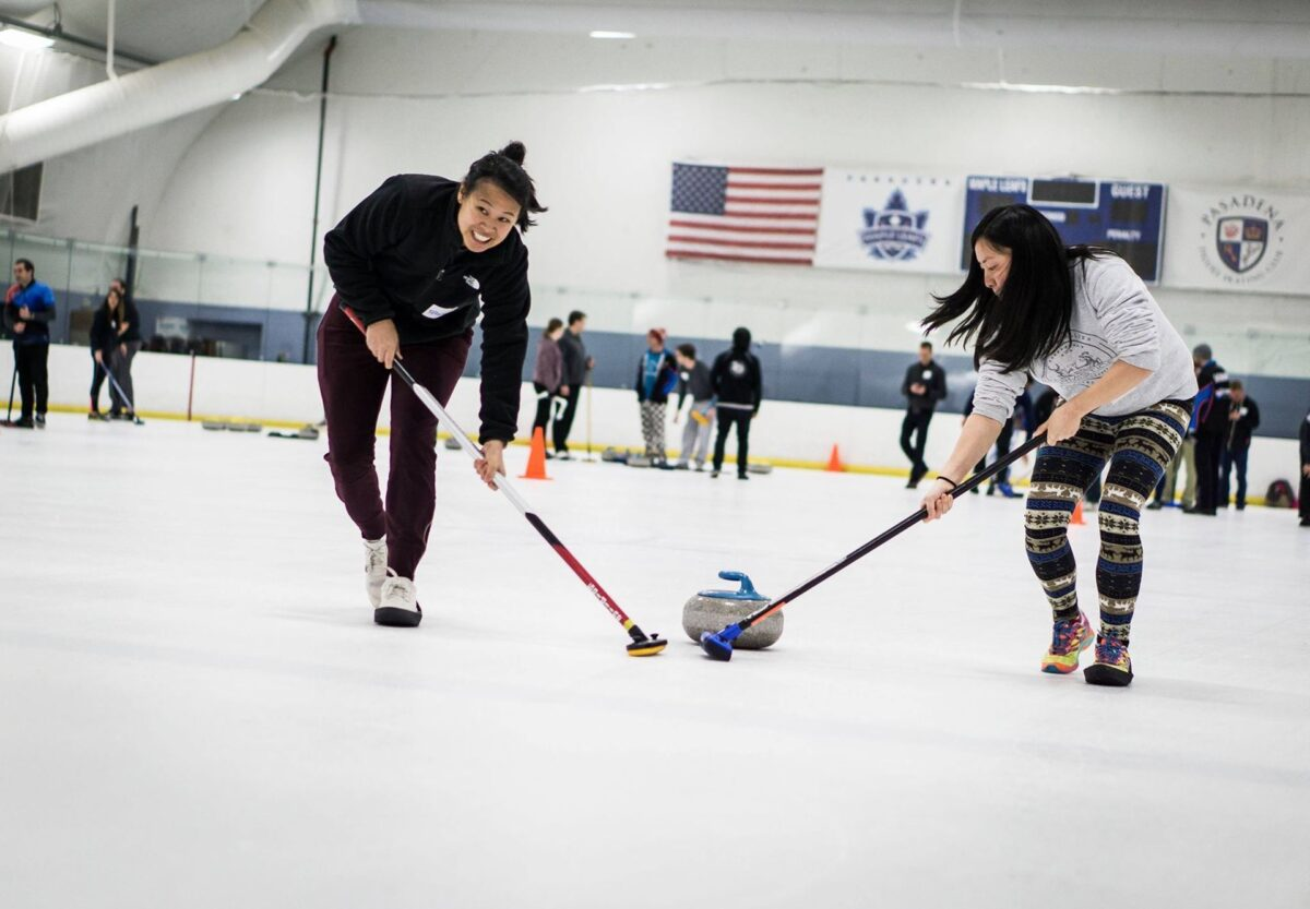 Two black-haired people sweeping in front of a curling stone on an ice rink.