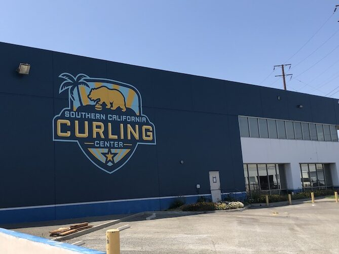 A large building with the Southern California Curling Center logo painted on a dark blue background.